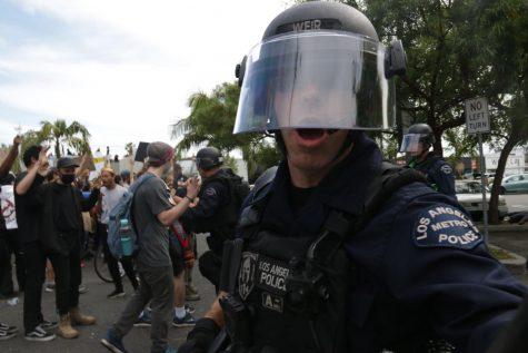 A police officer shoves protesters back.