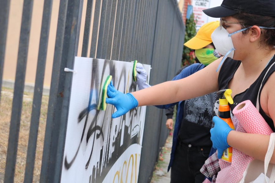 Participants wipe graffiti off of a sign in South Los Angeles