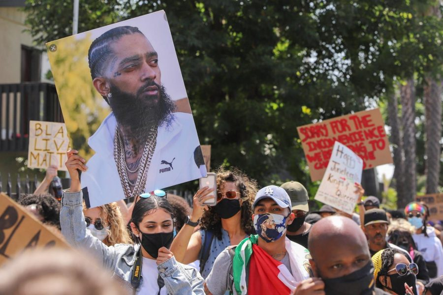 An individual holds a picture of late rapper and local hero Nipsey Hussle,  who was actively involved in uplifting his community.