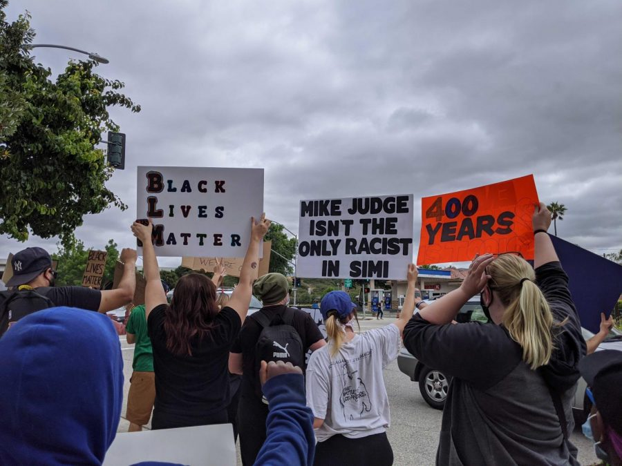Protesters hold signs as they march down Alamo Street toward the Simi Valley Police Department.