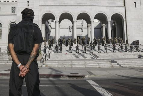 A man stands outside of City Hall.
