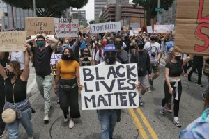 Protesters hold up signs as they walk in the streets.