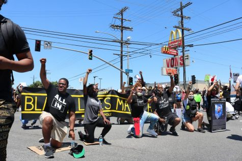 Organizers and protesters champion for change by kneeling in the intersection
