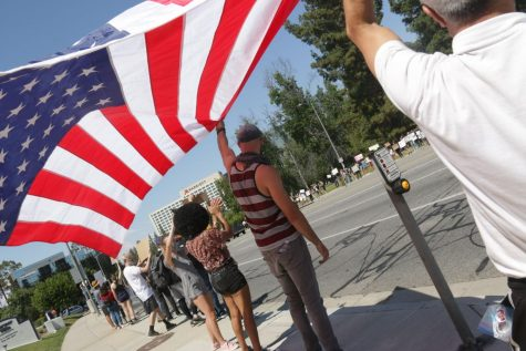 Protesters hold up an American flag upside down.