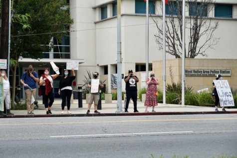 Protesters hold signs and chant outside West Valley Area Police Station.