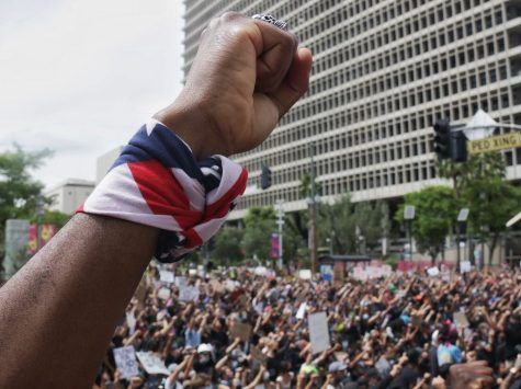 A protester holds up his fist as demonstrators hold a moment of silence for George Floyd outside of City Hall on May 31, 2020.
