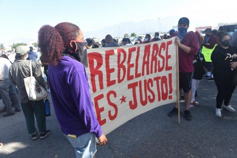 "Organizers from The People Struggles San Fernando Valley hold a banner that reads, ""To Rebel is Fair."""