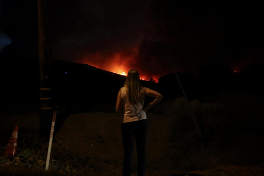 A woman watches the Lake Fire as it approaches her near the corner of Lake Hughes and Pine Canyon on Aug. 12.
