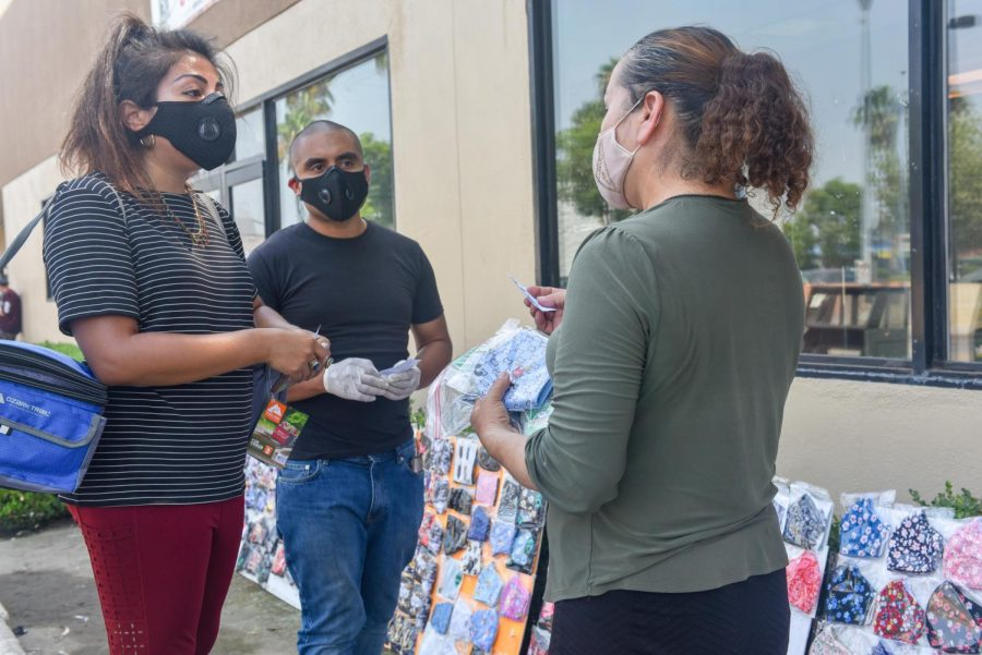 "Gaby Moreira-Rodriguez, a Las Calles Del Valle organizer, hands a vendor a protection package and a ""Know Your Rights"" information card, during a distribution in Panorama City, Calif."