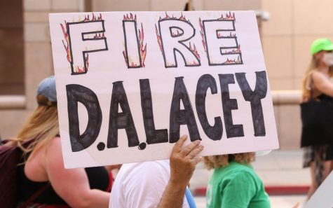A protester holds up a sign saying fire D.A. Lacey during a BLM protest against the district attorney, Jackie Lacey. Jackie Laceys husband, David Lacey, is charged with three counts of misdemeanor assault with a firearm on  Tuesday.