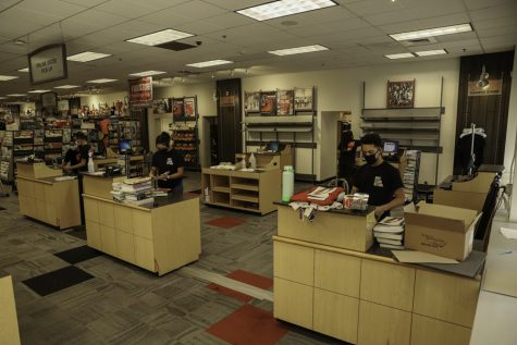 Bookstore employees putting together online orders from students at the CSUN Bookstore on Monday, Aug. 24, 2020. Students can order their books on the website and collect them at the store's pick-up section. All employees have masks on and tables set up to properly distance the customers and employees.