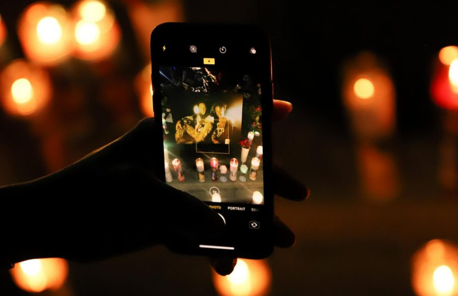 Tamika Bridgewater takes a photo of the candlelit memorial at the vigil for Ezekial