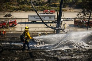 A LAFD firefighter sprays a chemical foam to prevent the fire from spreading further in Porter Ranch, Calif. on Saturday, Sept.4, 2020.