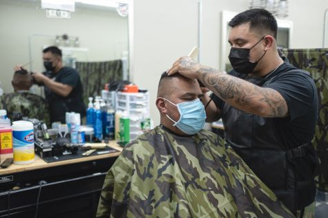 David Lopez, the owner of Modern Barber Room, cuts Jose Chavez