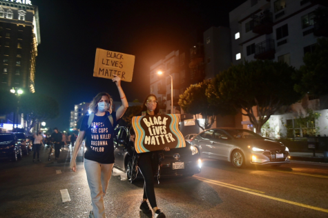 Two people walk through the streets of downtown Los Angeles on Sept. 23 protesting the grand jury decision of Breonna Taylor