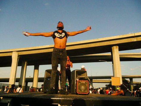 A man stands on a flatbed truck facing protesters as they march down Imperial Highway in South Los Angeles, Calif. on Saturday, Sept. 5, 2020.