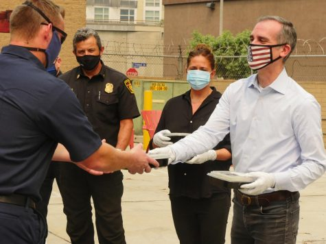 Mayor Eric Garcetti gives a firefighter food.