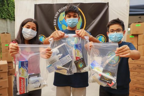 Sahara Karki, left, Nirvan Rayamajhi and Neil Rayamajhi hold up the hygiene kits for the homeless during their Bee The Hope packing event in Northridge, Calif., on Saturday, Sept. 12, 2020.