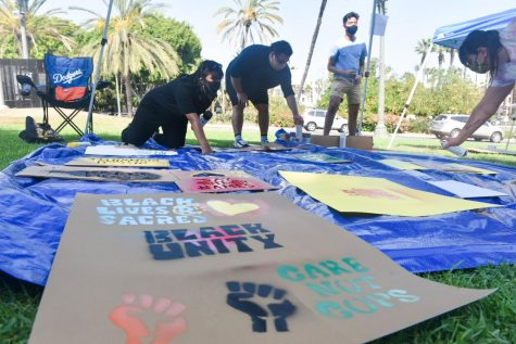 Participants spray painting on posters using stencils during the Artivism Community Day organized by the International Indigenous Youth Council on Sunday, Sept. 27, 2020.