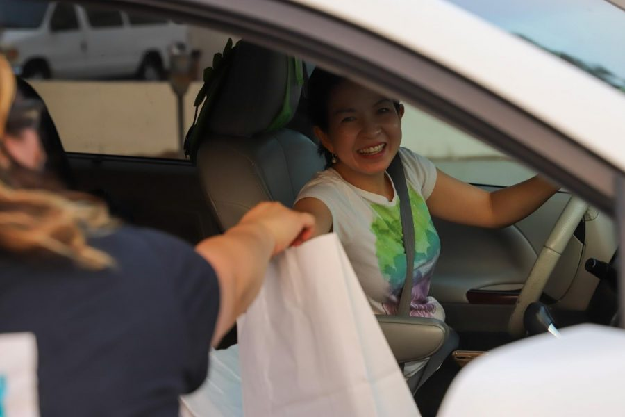 Lang Duong receives a bag with free school supplies for her grandchildren for the Free Back to School Event hosted by 818 Plates at Reseda, Calif., on Monday, Sept. 14, 2020.