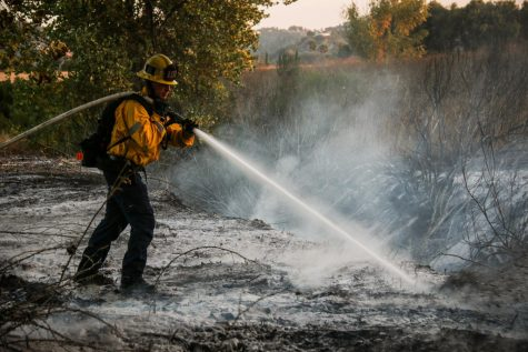 A firefighter sprays chemical foam to stop the fire from starting up again at the Sepulveda Basin Wildlife Reserve in Van Nuys on Saturday, Sept. 19, 2020.