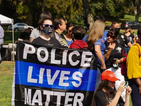 "A woman holds up a ""Police lives matter"" flag at a rally for police officers in Elysian Park on Saturday, Oct. 17, 2020."