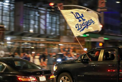 A Dodger fan waves a flag while driving through the intersection of Flower and 11th streets in downtown Los Angeles after the Dodgers won the World Series on Tuesday, Oct. 27, 2020.
