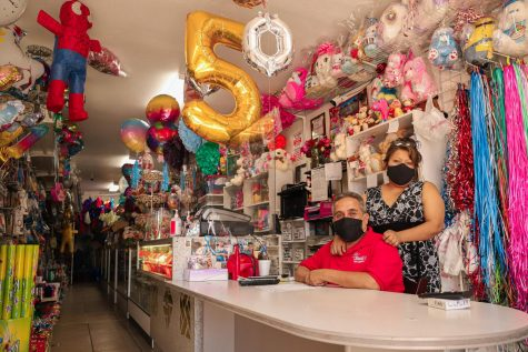 Claudia Paulino and Aurelio Rubio, the owners of Claudia's Party Store, sit at the cashier counter with their masks on in the store at Reseda, Calif., on Monday, Sept. 21, 2020.