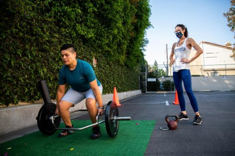 Rosangela Lunsford, left, attempts a deadlift while Evina Del Pizzo, the co-owner of Strong House Training, coaches her about proper deadlifting form during a private training session in the back parking lot of the training facility in Chatsworth, Calif., on Wednesday, Sept. 30, 2020.