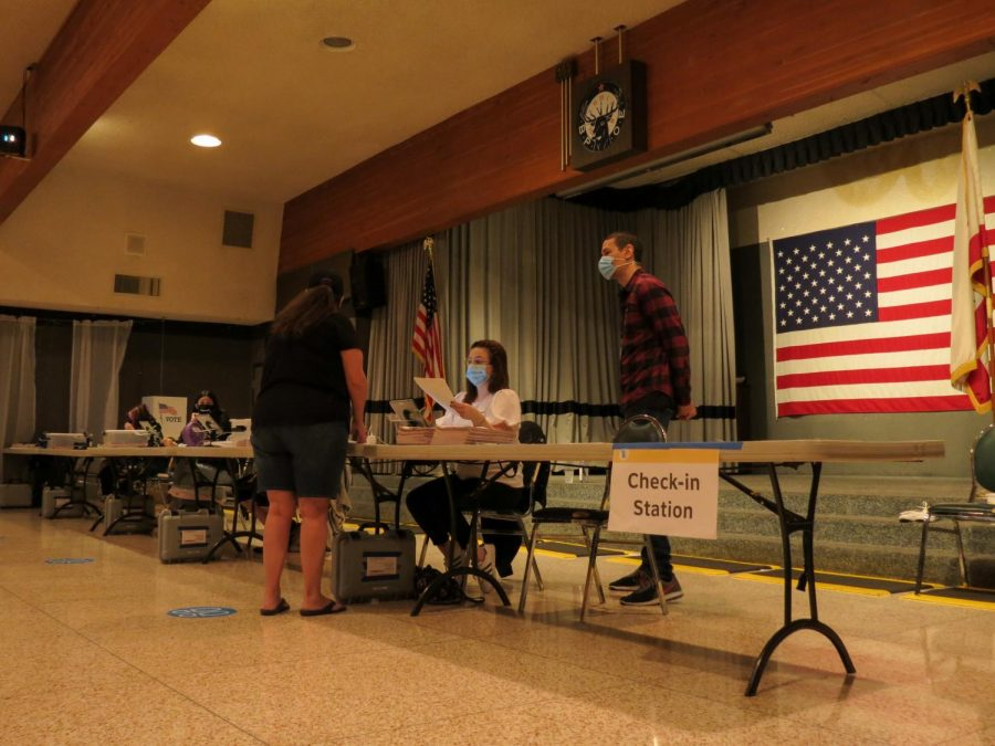 Poll workers helping to register a voter inside Elks Lodge in Canoga Park, Calif. on Election Day, Nov. 3, 2020.