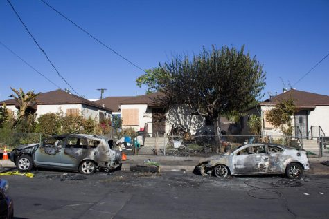 Two scorched cars are seen in front of residential homes after a single-engine plane crash near Whiteman Airport in Pacoima, Cali., on Thursday, Nov. 12, 2020. Neighbors pass by the cars days after the accident that left the pilot dead.
