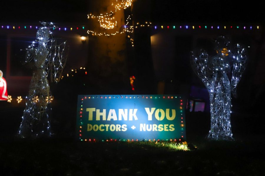 A sign decorated in colorful Christmas lights and angels says,