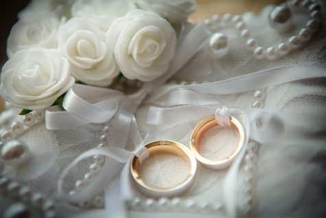 Two wedding rings with white flower in the background