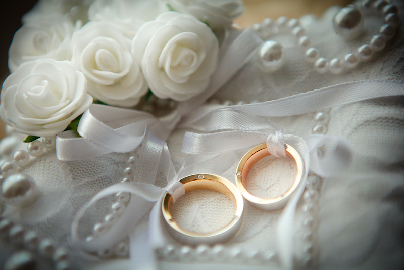 Two+wedding+rings+with+white+flower+in+the+background