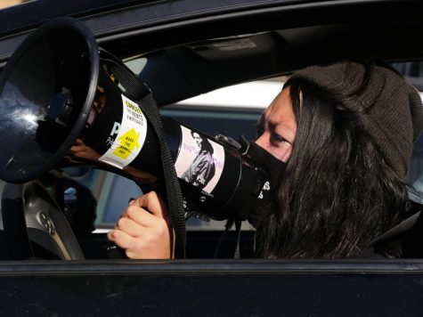 An activist speaks through a bullhorn during the car caravan protesting for the unhoused community on Monday, Jan. 18, 2020.
