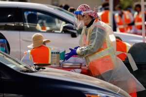 A worker at the CSUN COVID-19 vaccine distribution site prepares to administer a vaccination on  Tuesday, Jan. 19, 2021. Vaccinations are issued to the recipient while they are sitting in their car.