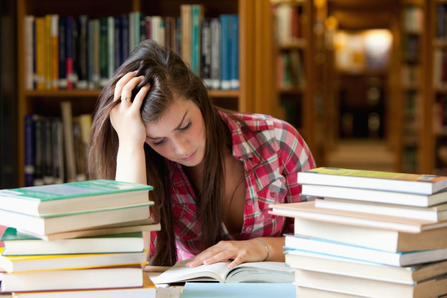 Focused+student+surrounded+by+books+in+a+library