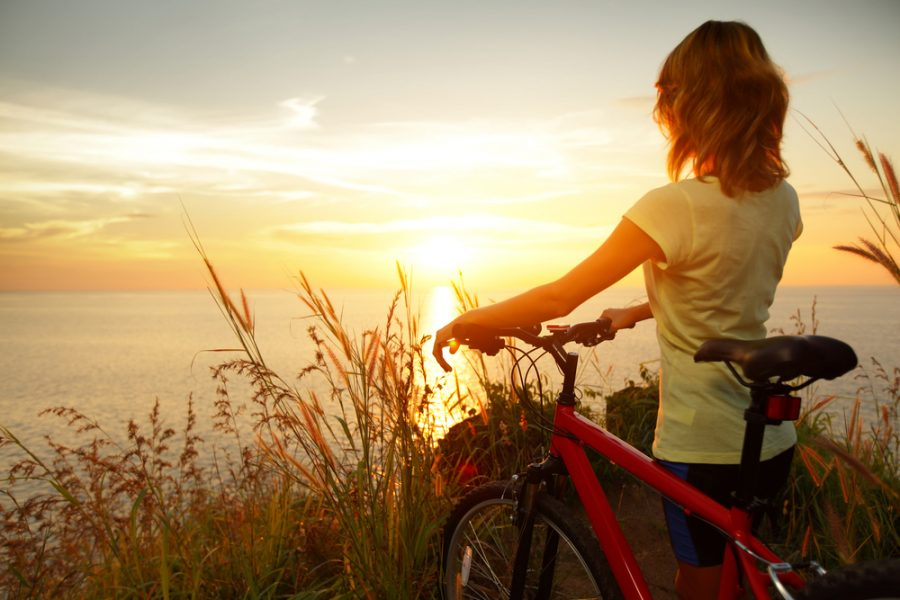 Young+lady+standing+with+bicycle+on+a+sea+coast+and+enjoying+sunset