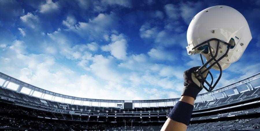 arm+holding+white+football+helmet+in+a+stadium