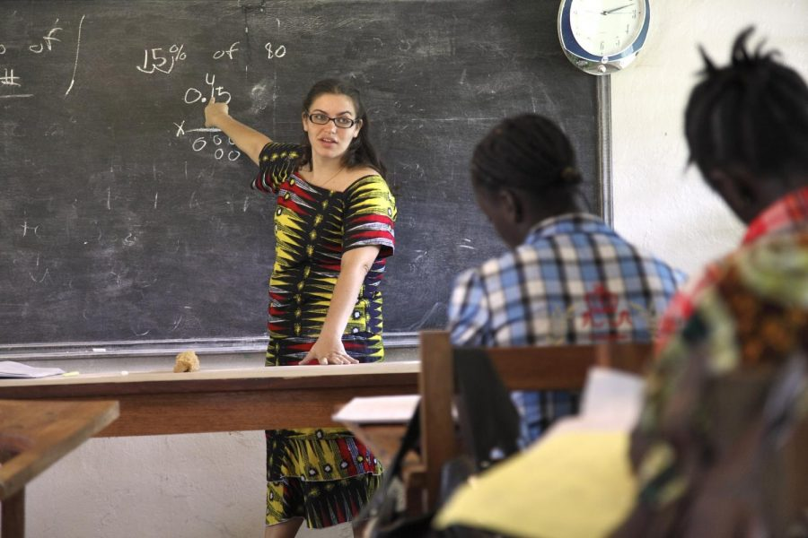 female teacher pointing at blackboard in front of students