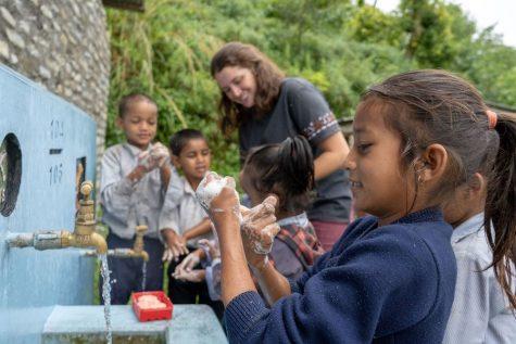 Children washing hands at an outdoor sink