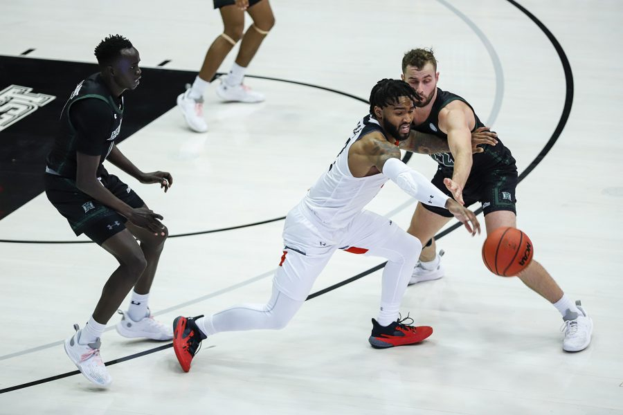 TJ Starks, middle, attempts to dribble around Hawai'i defenders, Junior Madut , left, and Casdon Jardine, right, during the first half of their game against the Hawai'i Rainbow Warriors at the Matadome on Friday, Feb. 19, 2021.