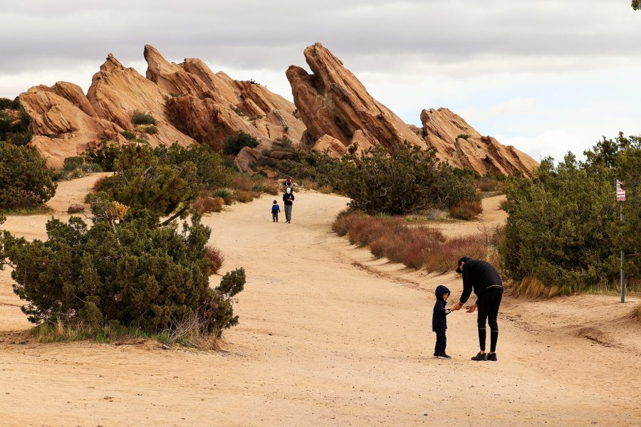 A father offers to carry his son the rest of the way while other families make their way back from climbing the beautiful natural structures in Vasquez Rocks Natural Area Park on Sunday, Feb. 14, 2021.