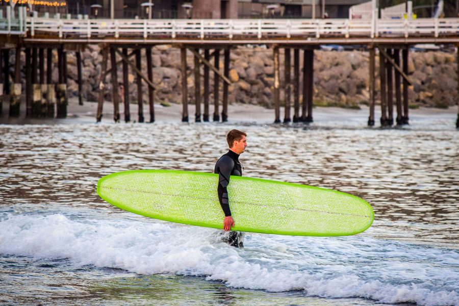 A surfer walks into the water at Surfrider Beach next to the Malibu Pier on Tuesday, Feb. 16, 2021.
