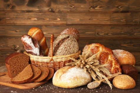 Different bread with sunflower seeds on wooden background
