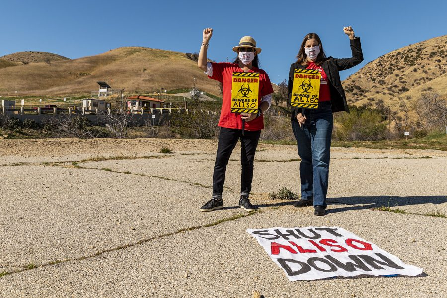 Porter Ranch residents and advocates against the Aliso Canyon Gas Storage Facility Jane Fowler, left, and Loraine Lundquist raise their fists and hold signs in front of the facility