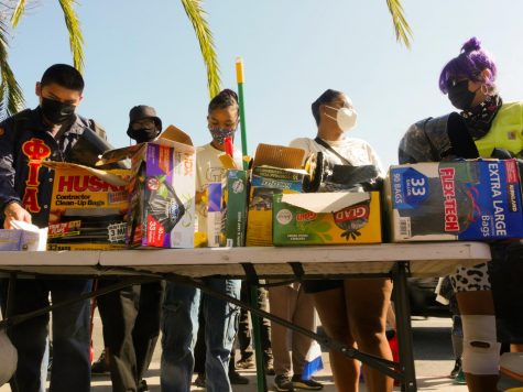 Clean-up participants pass out cleaning supplies in South Los Angeles on Saturday, Feb 27, 2021.