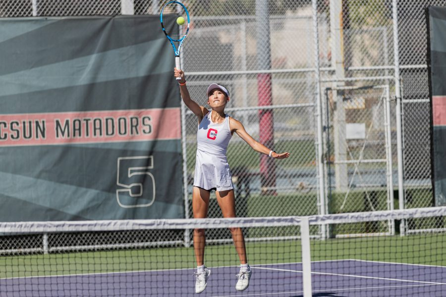 Jacquie Tan performs an overhead spike shot during her singles match against Olive Maunupau from the UC Davis Aggies at the Matador Tennis Complex in Northridge, Calif. on Sunday, March 28, 2021. Tan won in two sets with scores of 6-1 and 6-0.