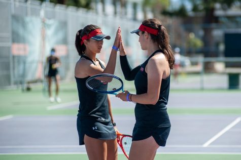 Doubles partners Jolene Coetzee, left, and Ana Toboso, right, celebrate during their doubles matchup against the Santa Clara Broncos at the Matador Tennis Complex in Northridge, Calif., on Saturday, March 27, 2021.