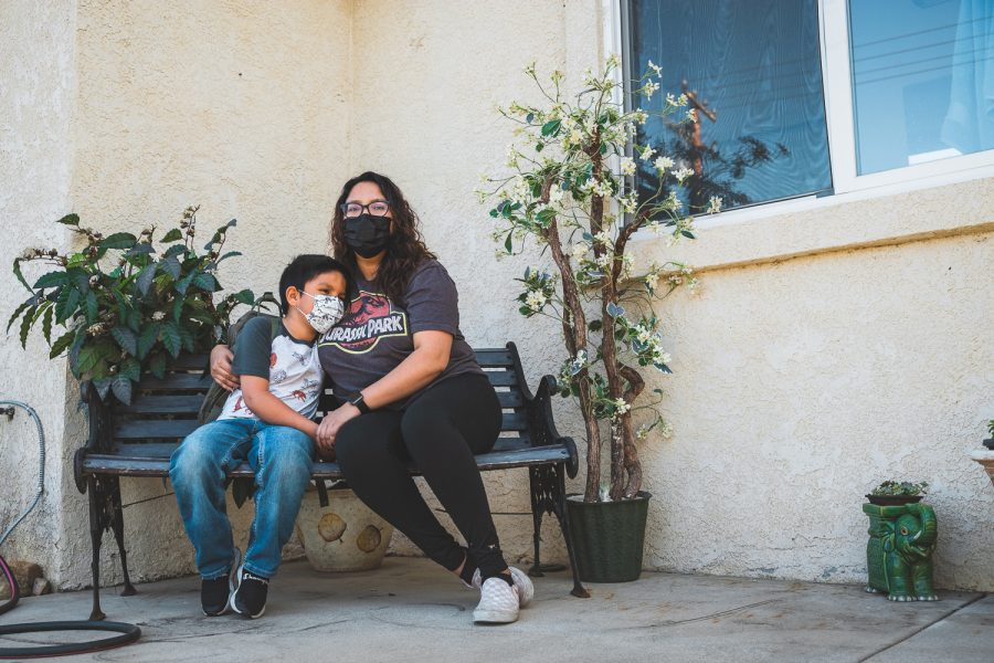 Rebecca Altamirano, right, embraces her son Sebastian while sitting on a bench outside of her boyfriends family home in Simi Valley, Calif., on April 1. 2021.